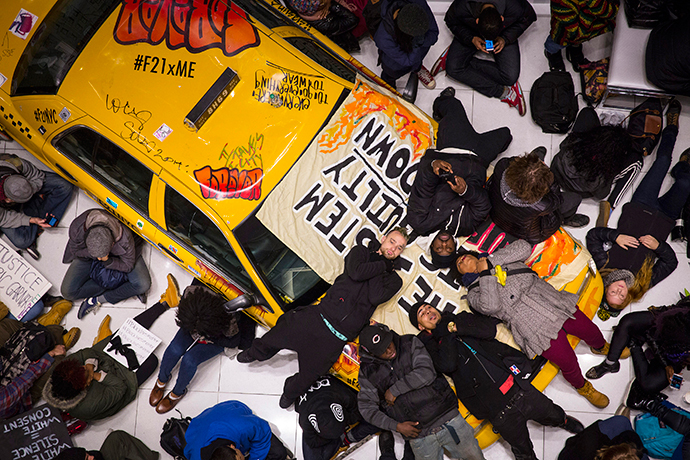 "Protesters stage a ""Die-In"" on a display taxi cab in the Forever 21 store in Times Square, during a march against police violence, in New York, December 7, 2014. (Reuters / Andrew Kelly)"