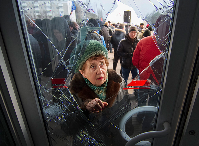 A woman looks through a damaged entrance door as pro-Russian demonstrators hold a rally outside the regional government building in Donetsk, March 3, 2014. (Reuters / Stringer)