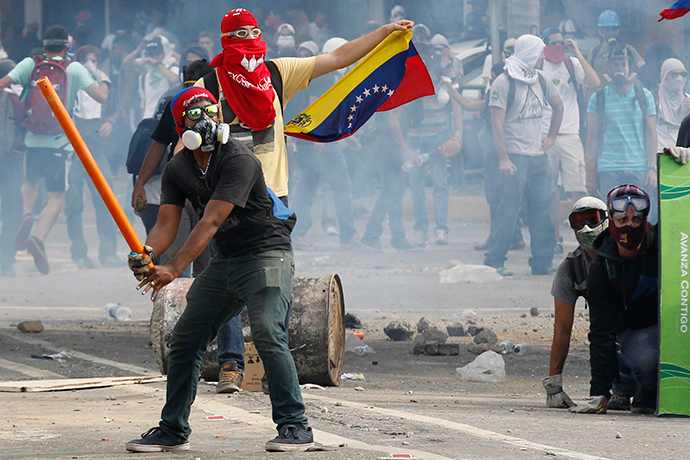 Anti-government demonstrators pretend to bat gas canisters to police during riots in Caracas April 1, 2014. (Reuters / Christian Veron)