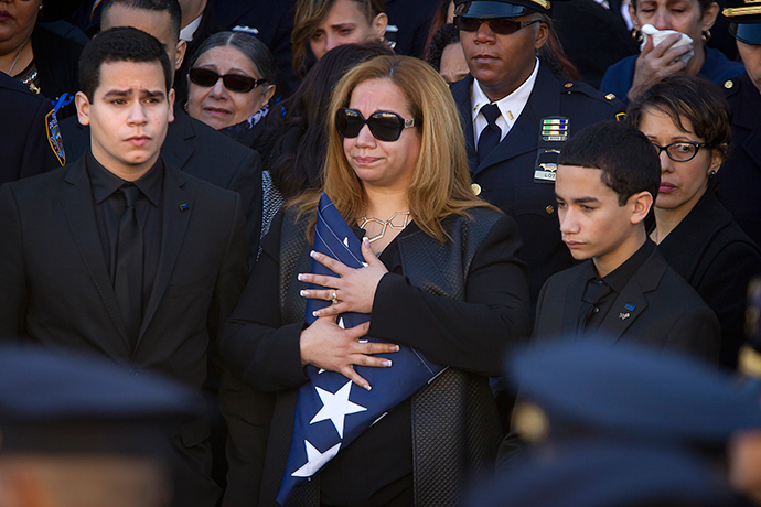 Justin Ramos (L) and Jaden Ramos ( R) flank their mother Maritza Ramos as she clutches a folded U.S. flag after the casket of their father, slain NYPD officer Rafael Ramos was loaded into a hearse at his funeral service at Christ Tabernacle Church to its final resting place in the Queens borough of New York December 27, 2014 (Reuters / Carlo Allegri)