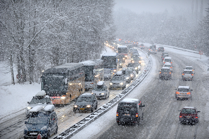 Snow fall as vehicles move bumper-to-bumper along the motorway near Albertville, on December 27, 2014 as they make their way into the Tarentaise valley in the heart of the French Alps, home to many of the famous French ski resorts. (AFP Photo / Jean-Pierre Clatot)