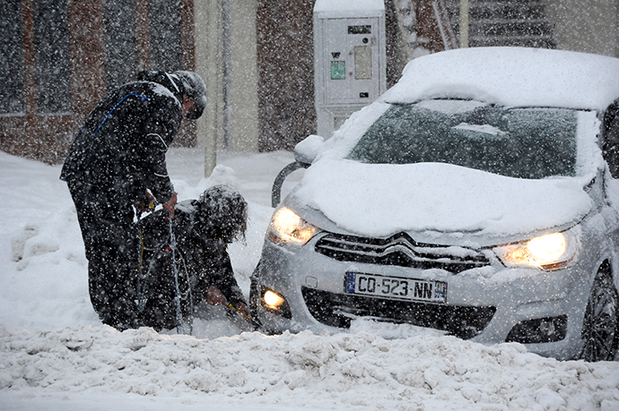 People put snow chains on their tires as snow falls on December 27, 2014 on the road to the Les Saisies ski resort in Savoie, central-eastern France. (AFP Photo / Jean-Pierre Clatot)