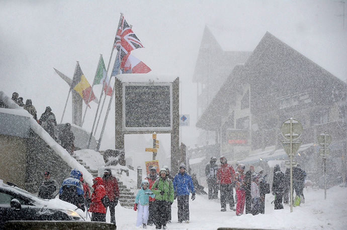 People walk at the Les Saisies ski resort in Savoie, central-eastern France, as snow falls on December 27, 2014. (AFP Photo / Jean-Pierre Clatot)