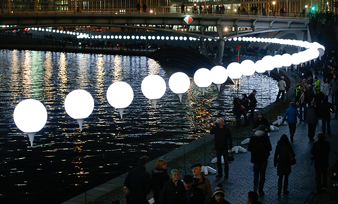 People walk under the lit balloons installation along the river Spree in Berlin November 8, 2014. (Reuters / Fabrizio Bensch)