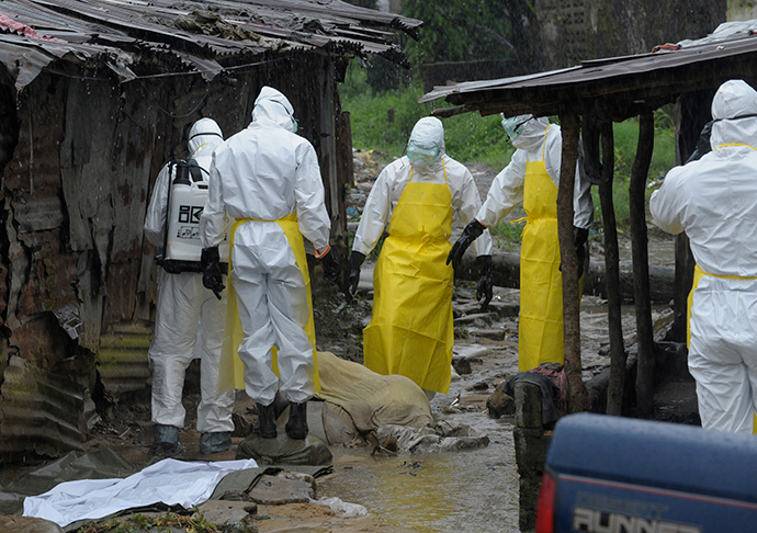 Health workers wearing protective clothing prepare to carry an abandoned dead body presenting with Ebola symptoms at Duwala market in Monrovia August 17, 2014. (Reuters / 2Tango)