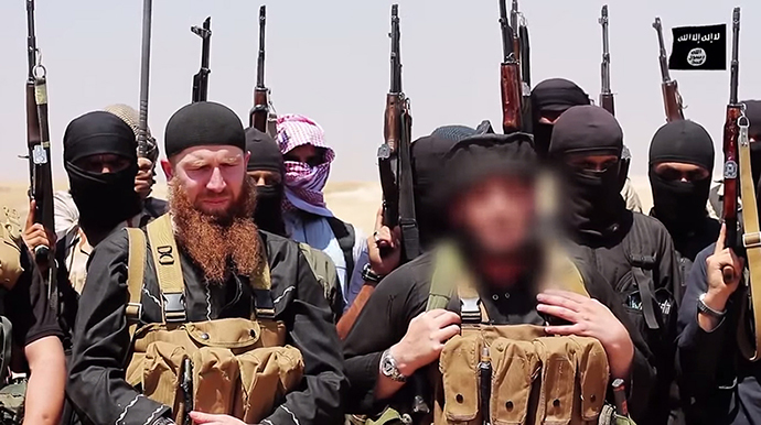 Members of the IS (Islamic state) including military leader and Georgian native, Abu Omar al-Shishani (Tarkhan Batirashvili) (C-L) and ISIL sheikh Abu Mohammed al-Adnani (C-R), whose picture was blurred from the source to protect his identity, speaking at an unknown location between the Iraqi Nineveh province and the Syrian town of Al-Hasakah on June 29, 2014. (AFP Photo / HO / Al-Itisam Media)