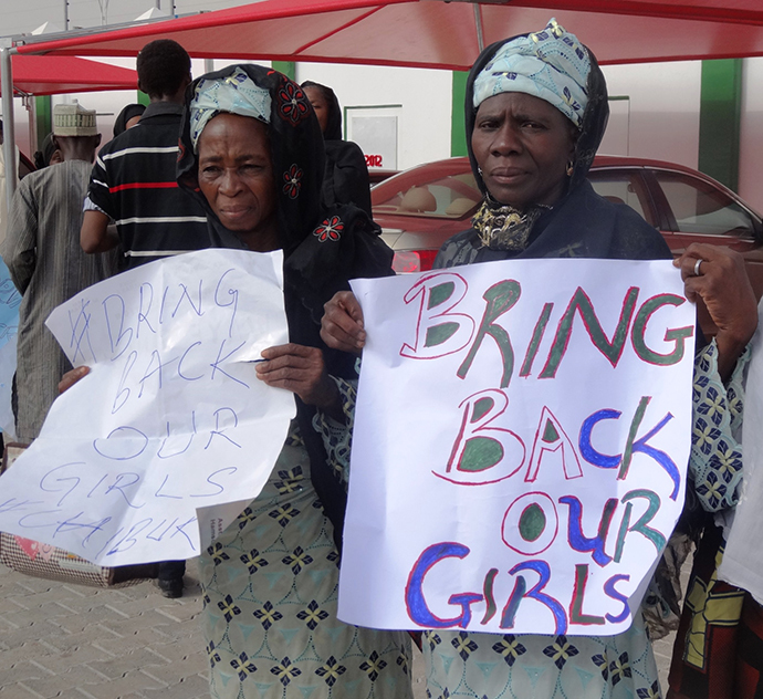 Two women in black veils display placards outside the governor's office in the northern Nigerian city of Kano on April 30, 2014, calling for the release of at least 187 school girls abducted by Boko Haram Islamists in northeastern town of Chibok in an April 14 raid on a girls boarding school. (AFP Photo / Aminu Abubakar)