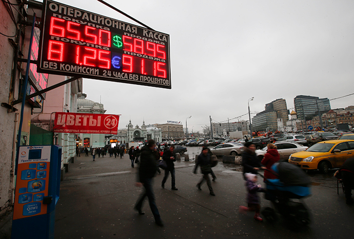 People walk past boards showing currency exchange rates in Moscow, December 17, 2014. The dramatic fall in Russia's rouble slowed on Wednesday, with the government selling foreign currency to prop it up after a 50 percent fall against the dollar this year. (Reuters / Maxim Zmeyev)
