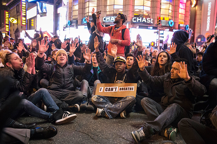 "Protesters, demanding justice for the death of Eric Garner, disrupt traffic while raising their hands during a ""sit-in"" at an intersection in Times Square, Manhattan, New York December 3, 2014. (Reuters / Elizabeth Shafiroff)"
