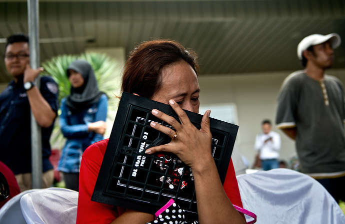 An Indonesian woman breaks down while holding a family picture of passengers onboard the missing Malaysian air carrier AirAsia flight QZ8501, outside the crisis-centre set up at Juanda International Airport in Surabaya on December 29, 2014. (AFP Photo/Manan Vatsyayana)