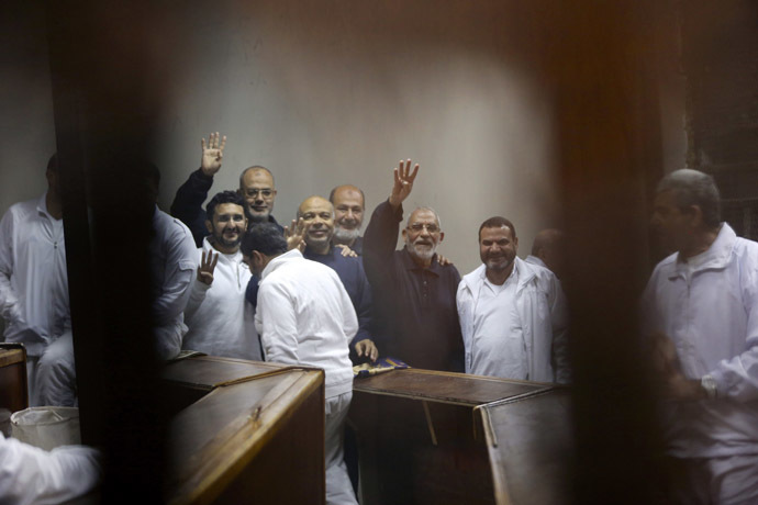 Muslim Brotherhood's Supreme Guide Mohamed Badie (3rd R) waves with the Rabaa sign, symbolizing support for the Muslim Brotherhood, with other brotherhood members at a court in the outskirts of Cairo December 14, 2014. (Reuters/Asmaa Waguih)