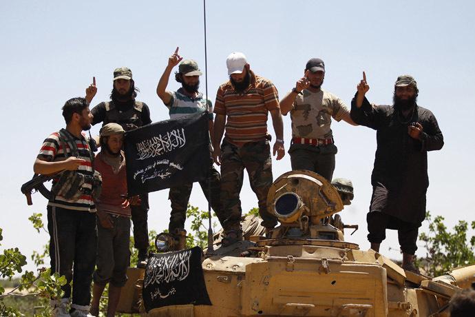 Islamist Syrian rebel group Jabhat al-Nusra members gesture while posing on a tank on Al-Khazan frontline of Khan Sheikhoun, northern Idlib province. (Reuters/Hamid Khatib)