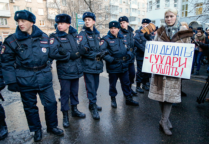 A supporter of opposition leader and anti-corruption blogger Alexey Navalny stands next to policemen blocking a street near a court building during his hearing in Moscow December 30, 2014 (Reuters / Tatyana Makeyeva)