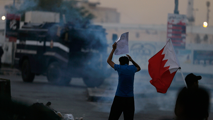 A protester holds an image of Al Wefaq Secretary-General Sheikh Ali Salman as he confronts a riot police armoured personal carrier during clashes between police and demonstrators protesting for Salman, in the village of Bilad Al Qadeem, south of Manama, December 29, 2014 (Reuters / Hamad I Mohammed)