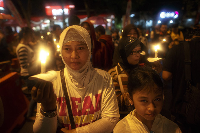Indonesians hold up candles during a candle light vigil for the victims of AirAsia flight QZ8501 at Surabaya December 31, 2014. (Reuters/Athit Perawongmetha)