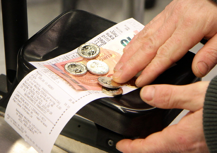 A customer pays in euro banknotes in a supermarket in Vilnius on January 1, 2015. (AFP Photo / Petras Malukas)
