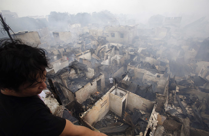 A man looks out from a veranda overlooking houses destroyed by a fire at a slum colony in Quezon city, Metro Manila January 1, 2015. (Reuters/Erik De Castro)