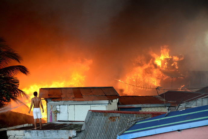 A man stands on a roof as he watches a fire engulfing a slum area in Manila on January 1, 2015. (AFP Photo)