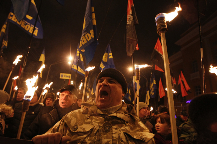 Activists of the Svoboda (Freedom) and Right Sector Ukrainian nationalist parties hold torches as they take part in a rally to mark the 106th birth anniversary of Stepan Bandera, one of the founders of the Organization of Ukrainian Nationalists (OUN), in Kiev January 1, 2015. (Reuters / Valentyn Ogirenko)