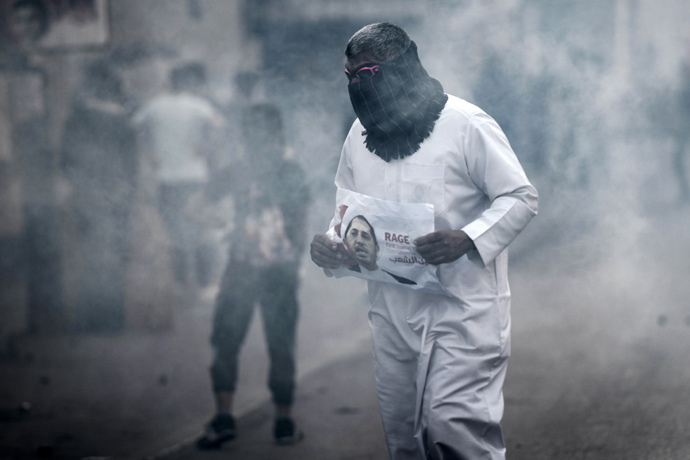A Bahraini protestor takes cover from tear gas during clashes with riot police following a protest against the arrest of the head of the banned Shiite opposition movement Al-Wefaq, Sheikh Ali Salman (on the poster) on January 1, 2015 in Bilad al-Qadeem, a suburb of Manama. (AFP Photo / Mohammed Al-Shaikh)