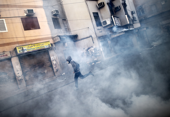 A Bahraini protestor runs for cover from tear gas during clashes with riot police following a protest against the arrest of the head of the banned Shiite opposition movement Al-Wefaq, Sheikh Ali Salman (on the poster) on January 1, 2015 in Bilad al-Qadeem, a suburb of Manama. (AFP Photo / Mohammed Al-Shaikh)
