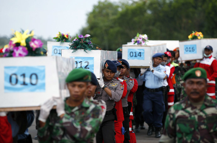 Caskets containing the remains of AirAsia QZ8501 passengers recovered from the sea are carried to a military transport plane before being transported to Surabaya, where the flight originated, at the airport in Pangkalan Bun, Central Kalimantan January 2, 2015. (Reuters/Darren Whiteside)