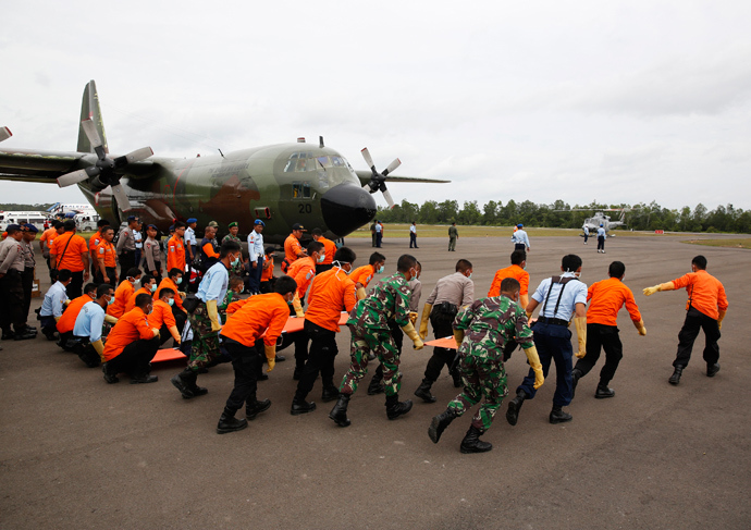 Indonesian Search and Rescue and security forces run to greet helicopters transporting the bodies of AirAsia QZ8501 passengers recovered from the sea at the airport in Pangkalan Bun, Central Kalimantan January 3, 2015 (Reuters / Darren Whiteside)