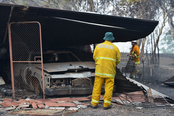 Country Fire Service volunteers work next to a burnt out shed near One Tree Hill in the Adelaide Hills, northeast of Adelaide on January 3, 2015 (AFP Photo / Brenton Edwards)