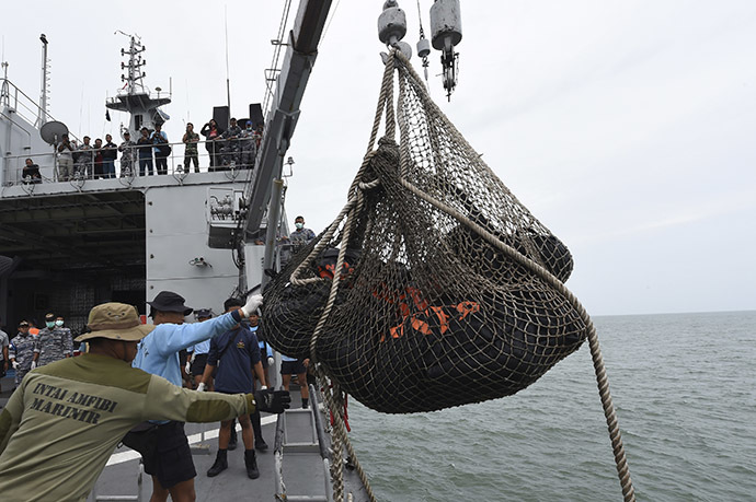 Personnel on the Indonesian Navy vessel KRI Banda Aceh lift body bags containing dead bodies recovered during a search operation for passengers of AirAsia flight QZ8501, at sea January 3, 2015. (Reuters/Adek Berry)