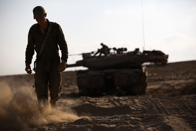 An Israeli soldier walks near his tank just outside the Israeli border with the northern Gaza Strip August 23, 2014 (Reuters / Amir Cohen)