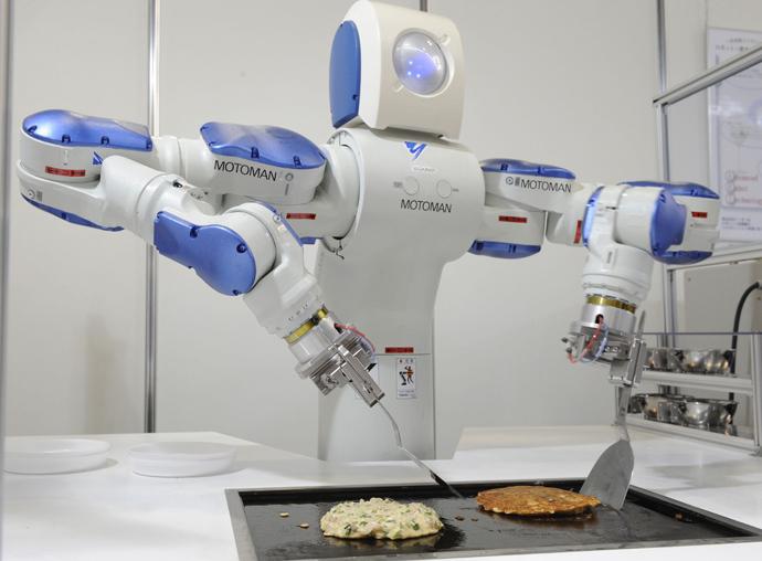 "ARCHIVE PHOTO: Japanese giant Yaskawa Electric's industrial robot Motoman turns over an ""okonomiyaki"", a Japanese pancake at a robot exhibition in Osaka. (AFP Photo / Yoshikazu Tsuno)"