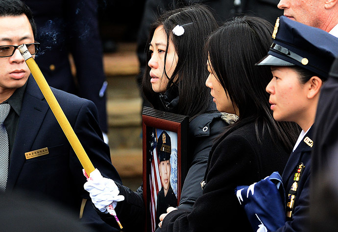 Pei Xia Chen (C), widow of New York Police Department (NYPD) officer Wenjian Liu, walks holding a picture of her husband during his funeral in New York's borough of Brooklyn on January 4, 2015. (AFP Photo/Jewel Samad)