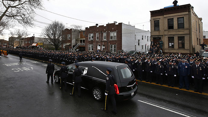A hearse carrying the casket containing New York Police Department officer Wenjian Liu makes its way in a procession down 65th Street following his funeral service in the Brooklyn borough of New York January 4, 2015. (Reuters/Mike Segar)