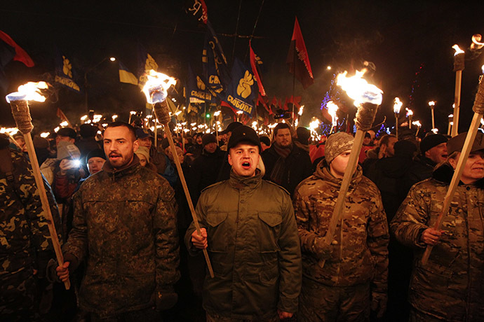 Activists of the Svoboda (Freedom) and Right Sector Ukrainian nationalist parties hold torches as they take part in a rally to mark the 106th birth anniversary of Stepan Bandera, one of the founders of the Organization of Ukrainian Nationalists (OUN), in Kiev January 1, 2015. (Reuters/Valentyn Ogirenko)