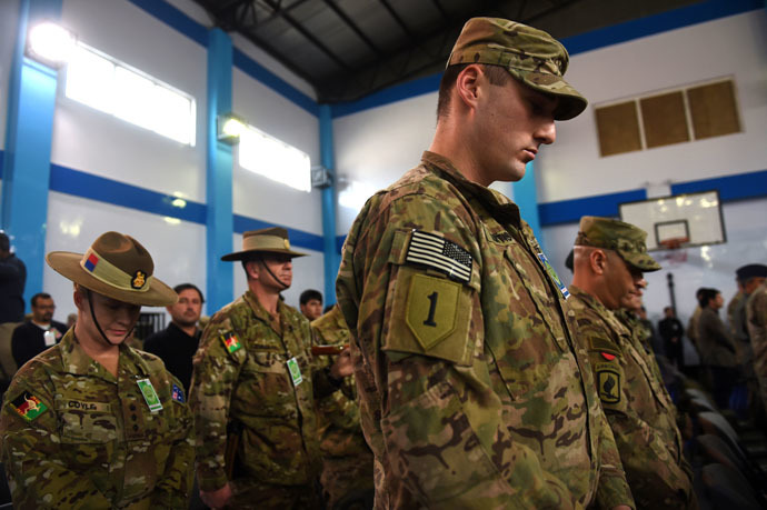NATO-led International Security Assistance Force (ISAF) bow their heads during a ceremony marking the end of ISAF's combat mission in Afghanistan at ISAF headquarters in Kabul on December 28, 2014. (AFP Photo/Shah Marai)