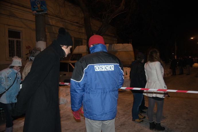 An OSCE representative seen outside the blown-up volunteer center in Odessa. (RIA Novosti/Denis Petrov)
