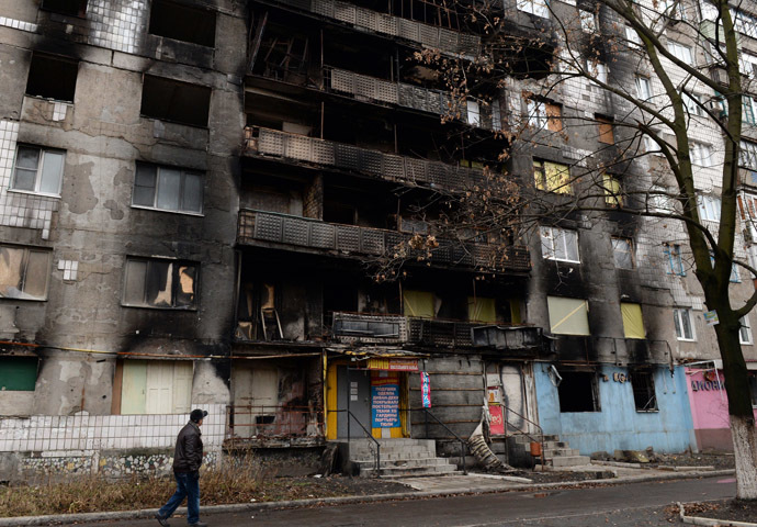 A man walks past the damaged residential building in the eastern Ukrainian city of Shakhtarsk on December 21, 2014. (AFP Photo/Vasily Maximov)