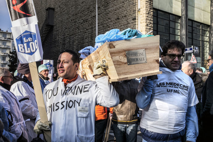 French general practitioners carry a coffin filled with medical outfits as they demonstrate, on January 5, 2015 in Lyon,s to protest against a upcoming health bill centred around a change to the system of payments. (AFP Photo)