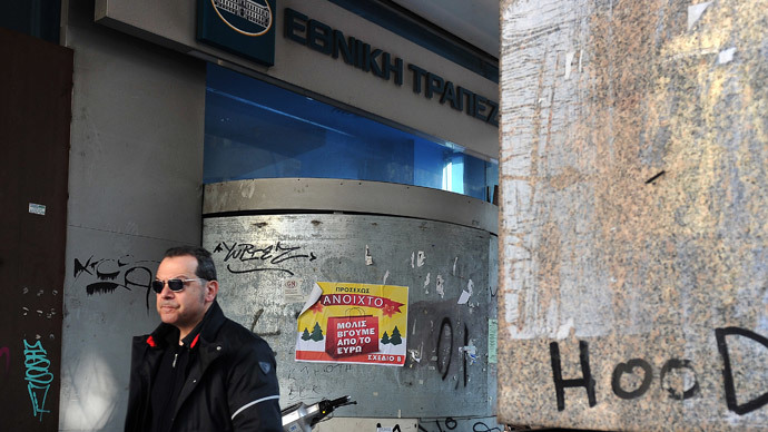 A man walks past a shut down National bank of Greece branch in central Athens, where a placard reads 'Open as soon as we exit the euro' by the 'Plan B ' political party on January 3, 2014. (AFP Photo / Louisa Gouliamaki)
