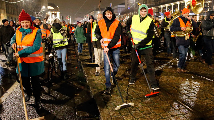 "Participants of an alternative rally use brooms as they protest against a demonstration called by anti-immigration group PEGIDA, a German abbreviation for ""Patriotic Europeans against the Islamization of the West"", in Dresden January 5, 2015.(Reuters / Fabrizio Bensch)"