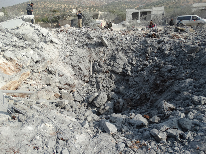 Syrians inspect a crater following a reported US-led coalition air strike in the town of Harem in the northwestern province of Idlib, bordering Turkey (AFP Photo / Mohamad Zeen)