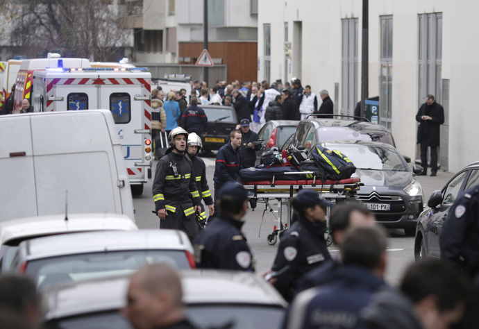 Firefighters push a stretcher outside the headquarters of the French satirical newspaper Charlie Hebdo in Paris on January 7, 2015, after armed gunmen stormed the offices leaving twelve dead, including three police officers, according to sources close to the investigation. (AFP Photo / Kenzo Tribouillard)
