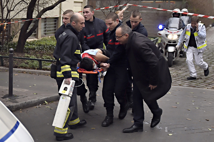 A victim is evacuated on a stretcher on January 7, 2015 after armed gunmen stormed the offices of the French satirical newspaper Charlie Hebdo in Paris, leaving at least 12 people dead. (AFP Photo / Martin Bureau)