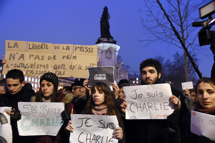 """A man holds a placard reading : """"Freedom of the press is priceless, fundamentalism, of any kind, will not pass"""" as others hold up placards reading in French, """"I am Charlie"""" during a gathering at the Place de la Republique (Republic square) in Paris, on January 7, 2015 (AFP Photo / Dominique Faget)"""