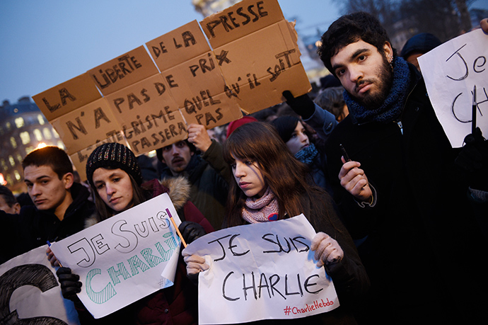 """A man holds a placard reading : """"Freedom of the press is priceless, fundamentalism, of any kind, will not pass"""" as others hold up pens and placards reading in French, """"I am Charlie"""" during a gathering at the Place de la Republique, following an attack by unknown gunmen on the offices of the satirical weekly, Charlie Hebdo (AFP Photo / Martin Bureau)"""