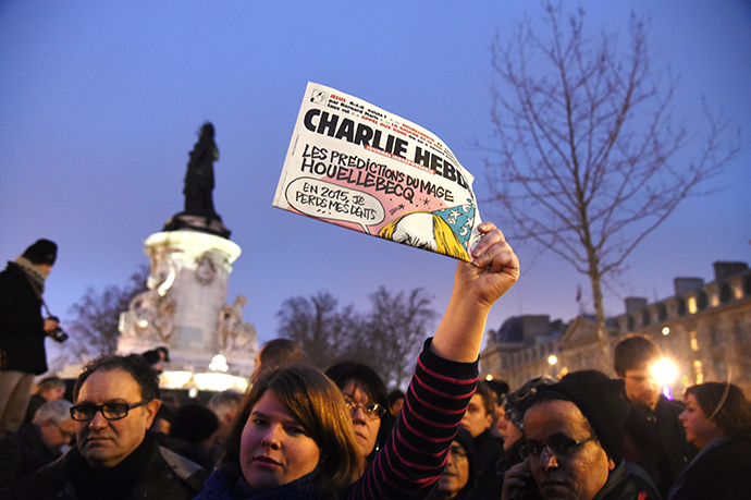 A woman holds up the satirical weekly Charlie Hebdo during a gathering at the Place de la Republique in Paris, on January 7, 2015 (AFP Photo / Dominique Faget)