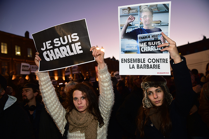 "Women hold placards reading ""I am Charlie"" (L) and ""Together against barbarism"" in Toulouse on January 7, 2015 (AFP Photo / Eric Cobanis)"