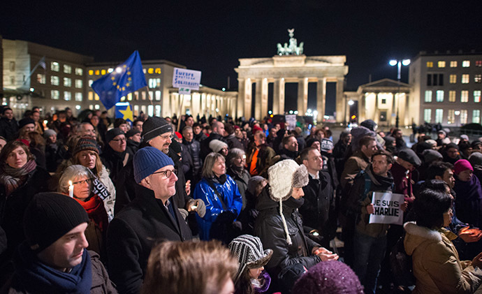 People stand near Berlin's landmark the Brandenburg Gate during a spontaneous vigil outside the French embassy on January 7, 2015 in Berlin to express solidarity with employees of the French satirical weekly Charlie Hebdo that has been target of an attack by unknown gunmen. (AFP Photo/Bernd Von Jutrczenka)