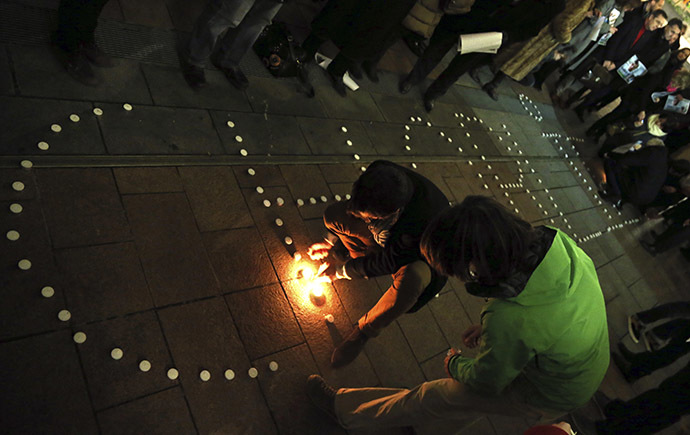 "People try to light candles to form the word ""Charlie"" to pay tribute to the victims of a shooting by gunmen at the offices of weekly satirical magazine Charlie Hebdo in Paris, in front of the European Parliament in Brussels January 7, 2015. (Reuters/Francois Lenoir)"