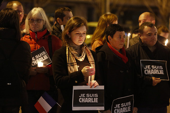 People hold a vigil for the victims of the shooting at the Paris offices of the publication Charlie Hebdo outside the French consulate in Seattle, Washington January 7, 2015. (Reuters/Jason Redmond)